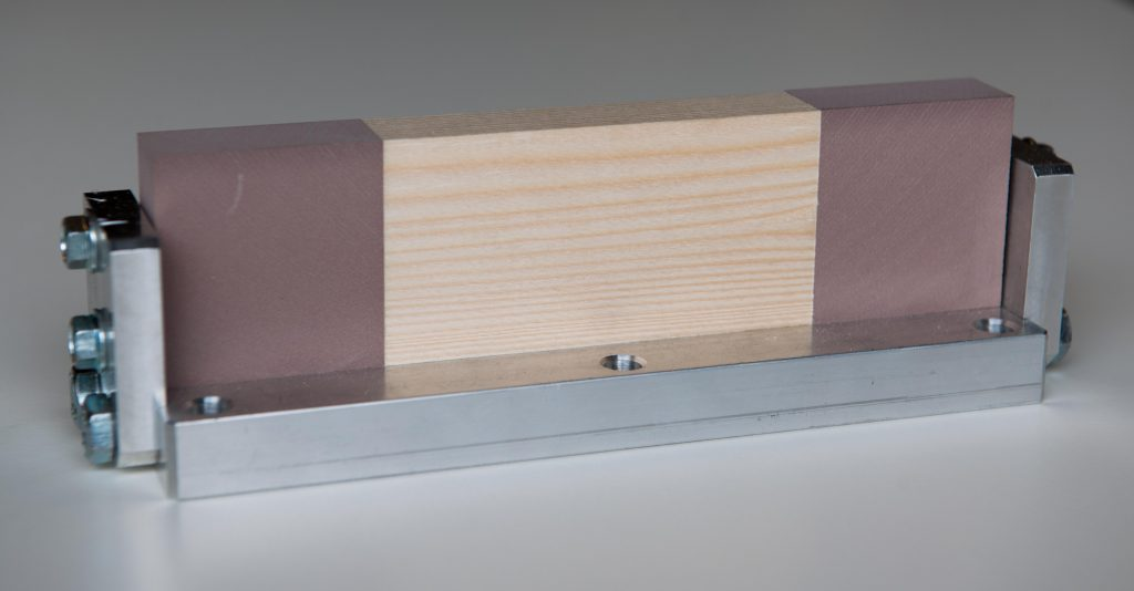Držák vzorku se vzorkem dřeva upnutým mezi dva PUR bloky